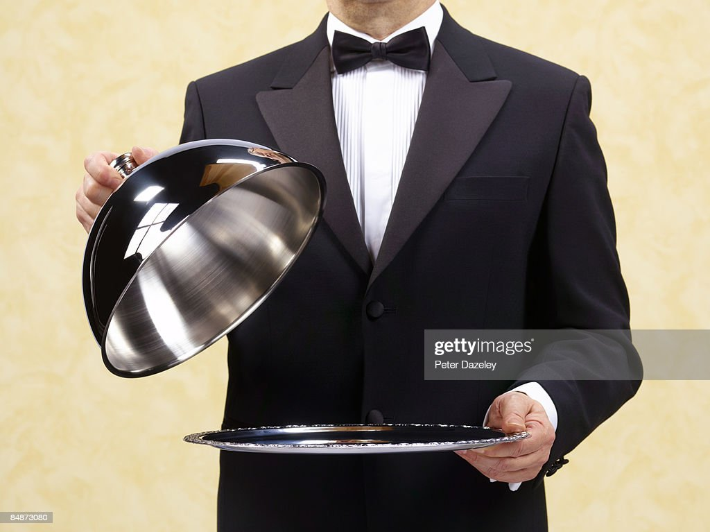 Butler waiter holding open domed silver tray. : Stock Photo
