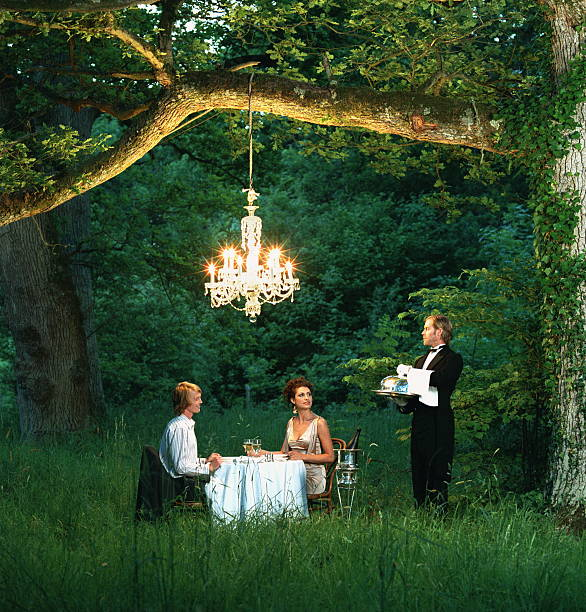 Butler Waiting On Young Couple Dining At Table In Forest Wall Art
