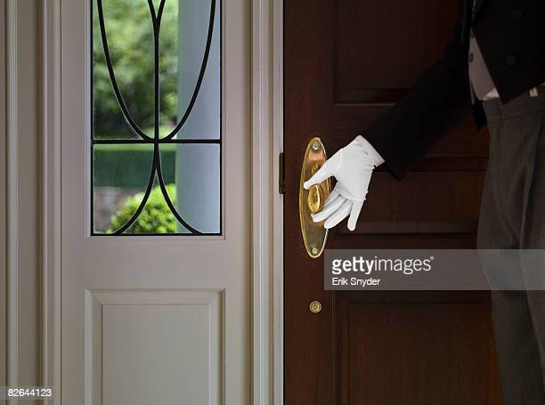 Butler with hand on front door knob.