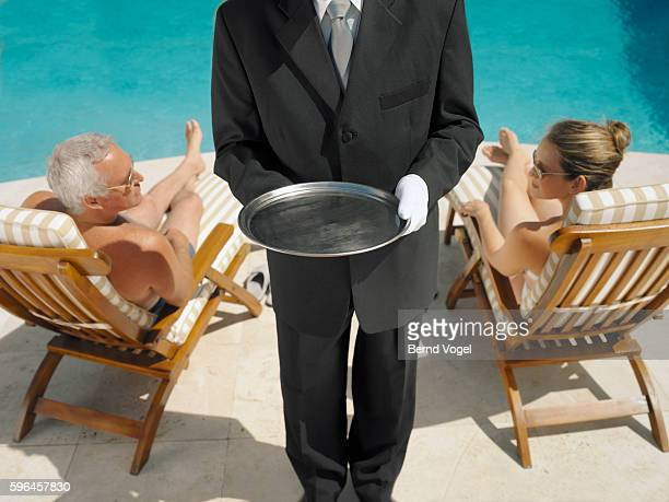 Butler with hotel guests by the swimming pool