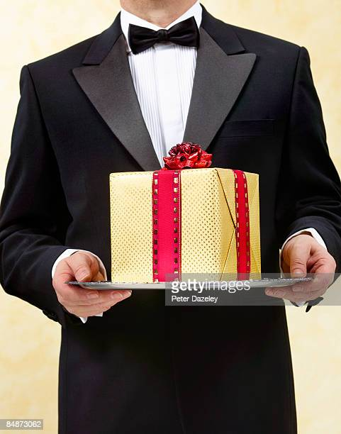 butler with wrapped present on silver tray, salver - dinner jacket stock pictures, royalty-free photos & images