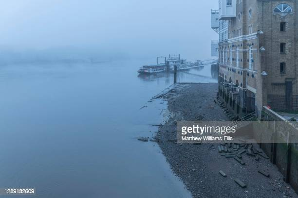 Butlers Wharf Pier at low tide with a River Thames beach in thick foggy and misty moody weather in London city centre during Covid-19 Coronavirus...
