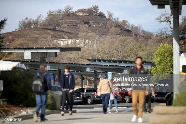 Butte College students walk on campus as classes resume following the Camp Fire while a hillside behind the school shows just how close the wildfire...