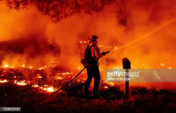 Butte county firefighter douses flames at the Bear fire in Oroville, California on September 9, 2020. - Dangerous dry winds whipped up California's...
