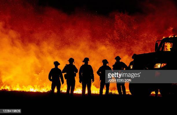 Butte County firefighters watch as flames quickly spread across a road at the Bear fire in Oroville, California on September 9, 2020. - Dangerous dry...