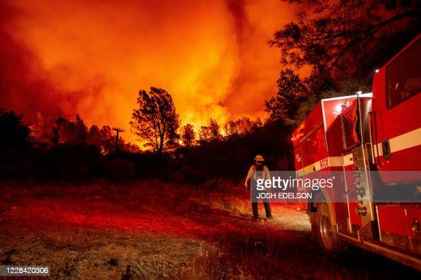 Butte county firefighters watch as flames tower over their truck at the Bear fire in Oroville, California on September 9, 2020. - Dangerous dry winds...