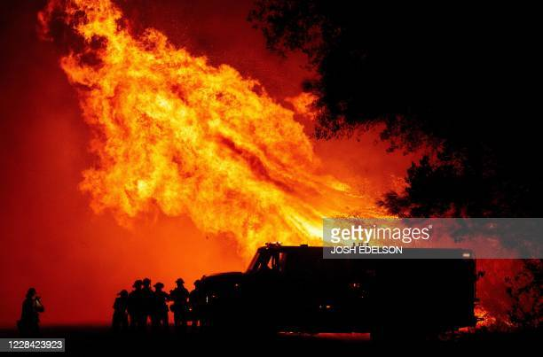 Butte county firefighters watch as flames tower over their truck during the Bear fire in Oroville, California on September 9, 2020. - Dangerous dry...