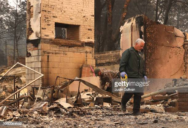 Butte County sherriff deputy searches the property of a destroyed home for a reported Camp Fire victim on November 10 2018 in Paradise California...