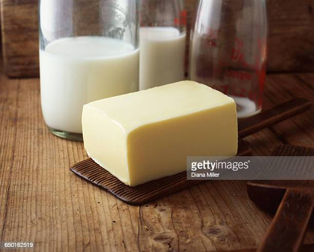 Butter block with milk bottles on wooden table