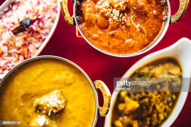 butter chicken, lamb curry, vegetable curry and basmati rice on a table. north indian food - north indian food stock photos and pictures