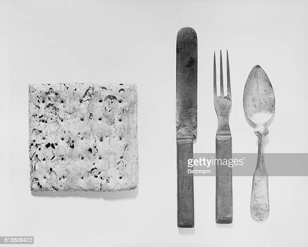 A butter knife fork and spoon from the mess kit of a Union soldier alongside a hardtack bread made from only flour and water