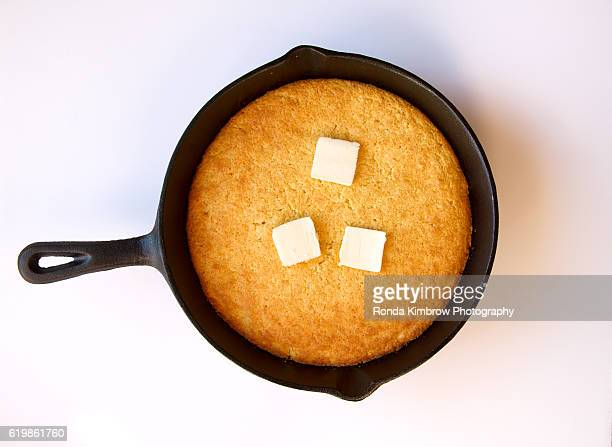 Butter melting on cornbread cooked in a cast iron skillet isolated on white background
