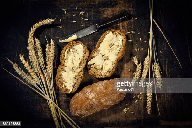 Buttered bread and ear of wheat on dark wood