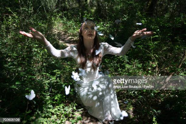 Butterflies Flying Over Woman Sitting With Arms Raised At Forest