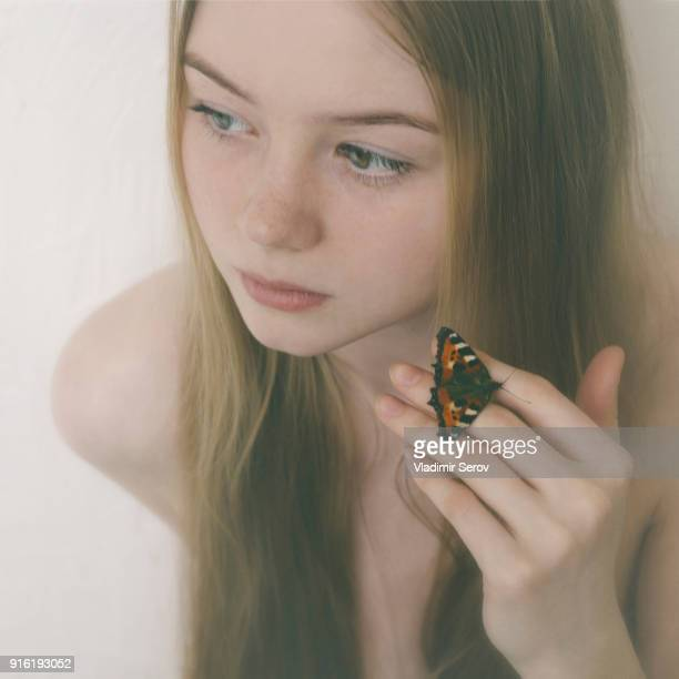 Butterfly on fingers of Caucasian teenage girl