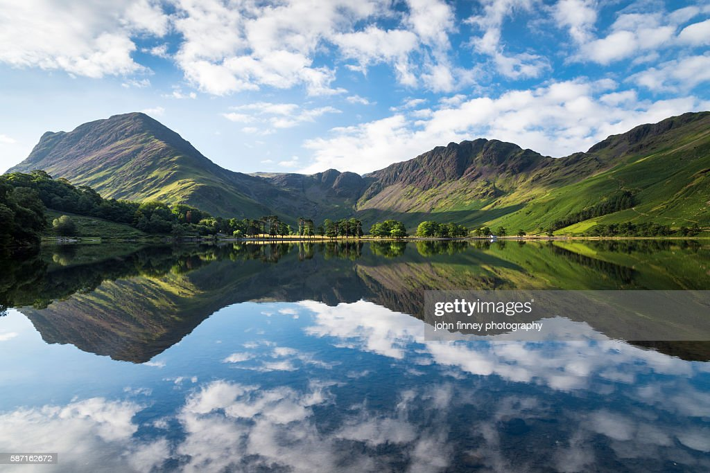 Buttermere lake early morning reflections. A beautiful summer morning with Fleetwith Pike and Haystacks mountains covered in purple heather. Lake District National park. UK. Europe. : Stock Photo