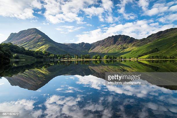 buttermere lake early morning reflections. a beautiful summer morning with fleetwith pike and haystacks mountains covered in purple heather. lake district national park. uk. europe. - lake district stockfoto's en -beelden