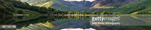 Buttermere lake reflections. Panoramic image taken on lake Buttermere on a beautiful summer morning. Cumbria. Lake District National park. UK. Europe.