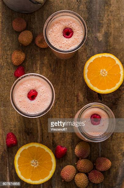 Buttermilk smoothie, orange, litchi and raspberries on wood