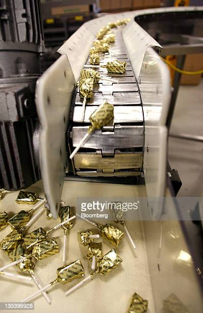 Butterscotch lollipops move along a conveyor belt before being packaged at the See's Candies Inc lollipop factory in Burlingame California US on...