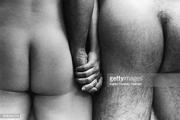 Buttocks of a Nude Couple Holding Hands