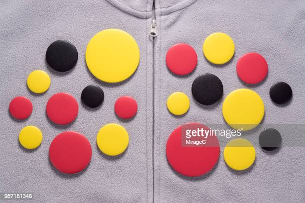 button badges on gray jacket - brooch stock pictures, royalty-free photos & images