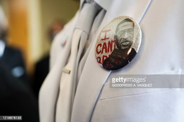 I button that reads I can't breathe adorns the jacket of a mourner before the funeral for George Floyd on June 9 at The Fountain of Praise church in...