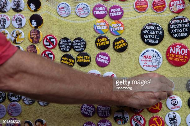Buttons against President Michel Temer and pension reform are displayed for sale during a protesT in Sao Paulo Brazil on Monday Feb 19 2018 There may...