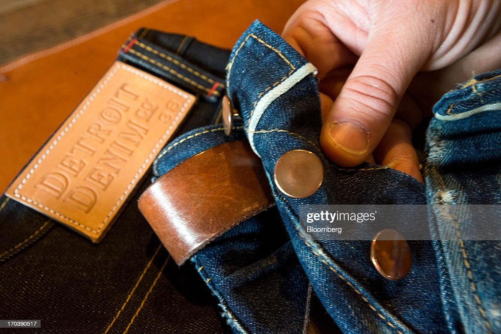 Buttons and rivets, made of copper, are displayed for a photograph by an employee at Detroit Denim, in Detroit, Michigan, U.S., on Wednesday, June 12, 2013. The Commerce Department is scheduled to release monthly business inventories data on June 13. Photographer: Ty Wright/Bloomberg via Getty Images