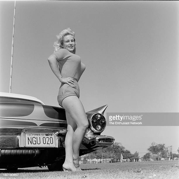 A buxom blonde poses provocatively next to a heavily customized 1957 Ford TBird
