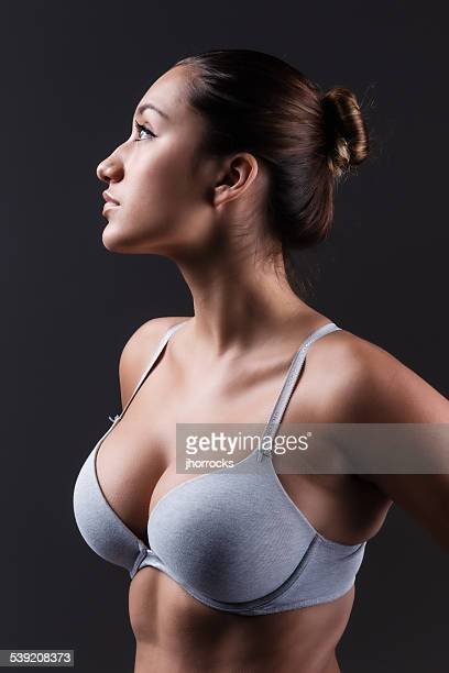 buxom young woman in gray bra - bare breasted babes stock pictures, royalty-free photos & images