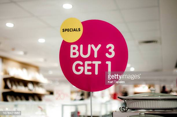 "a ""buy 3, get 1"" sign on a shopping mall - reduction stock pictures, royalty-free photos & images"