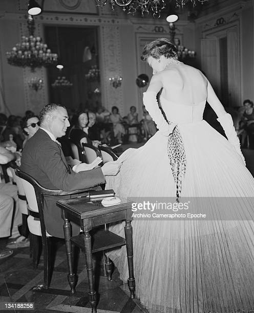 A US buyer examines one of the dresses on show at the AutumnWinter 19511952 fashion show in Florence 21st July 1951