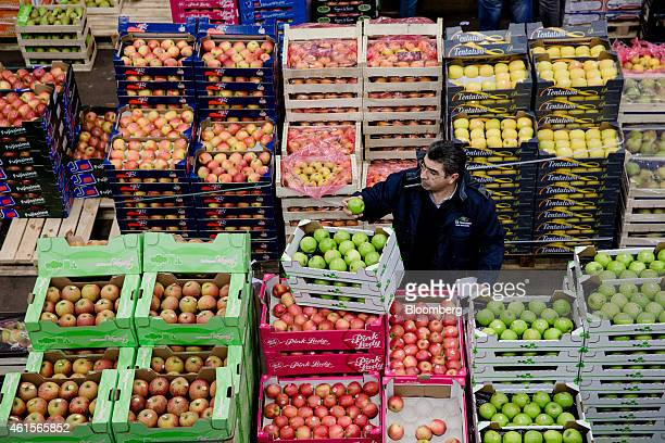 A buyer inspects a green apple as he stands beside crates of fresh produce in the fruit and vegetable section of Rungis wholesale food market in...