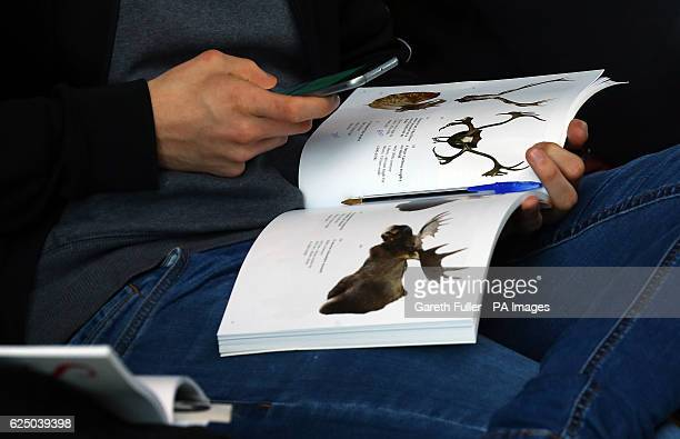 A buyer photographs an item in an auction catalogue before the sale of a rare nearcomplete Dodo skeleton which sold for a total of pound346300 at...