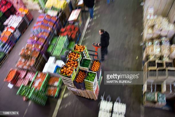 A buyer pulls a trolley on December 20 2012 in the vegetable section at the international wholesale market in the southern Paris suburb of Rungis The...