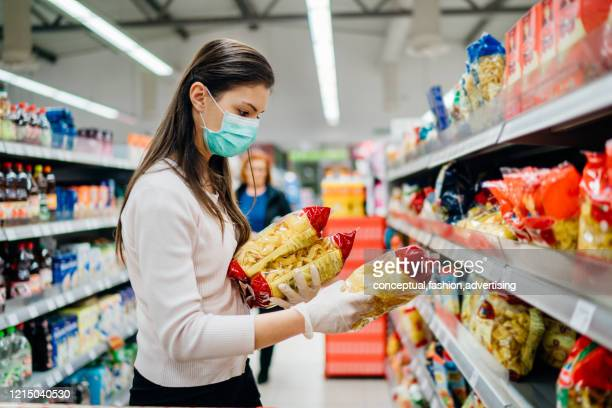 buyer wearing a protective mask.shopping during the pandemic quarantine.nonperishable smart purchased household pantry groceries preparation.woman buying few pasta packages.budget pastas and noodles. - consumentisme stockfoto's en -beelden