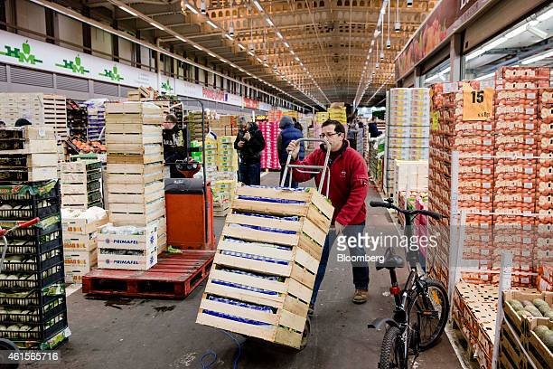 A buyer wheels crates of fresh produce with a trolley in the fruit and vegetable section of Rungis wholesale food market in Rungis France on Thursday...
