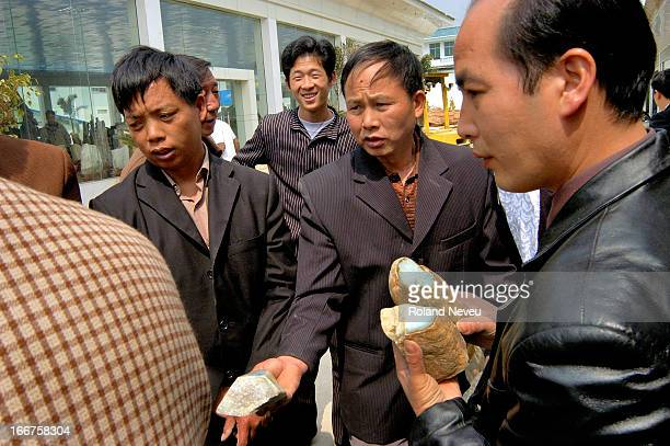 Buyers and sellers trading at a market for jade and petrified wood from Burma in the Special Economic Zone of Ruilli