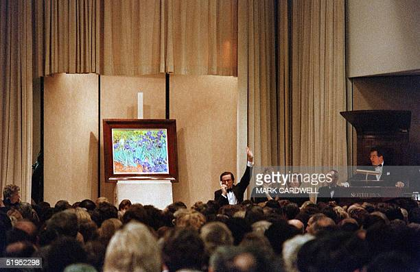 """Buyers bid by telephone for Vincent van Gogh's """"Irises"""" at an auction at Sotheby's in New York 11 November 1987, where the painting sold for a record..."""