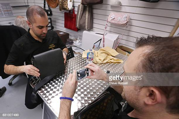 TORONTO ON NOVEMBER 25 Buyers examine a pair of men's Louis Vuitton hand bags that came in They will example the bags looking at quality and for the...