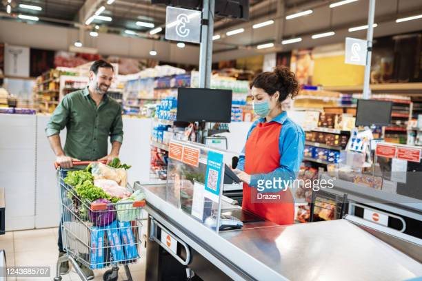 buyers with protective face mask in supermarket during coronavirus covid-19 pandemic - assistant stock pictures, royalty-free photos & images
