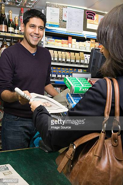 buying a newspaper - convenience store counter stock photos and pictures