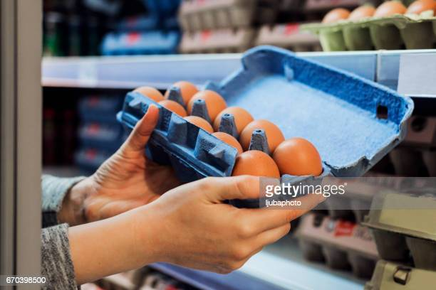 buying eggs in a supermarket - carton stock pictures, royalty-free photos & images