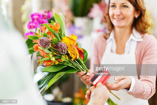 Buying flower in a flower shop.