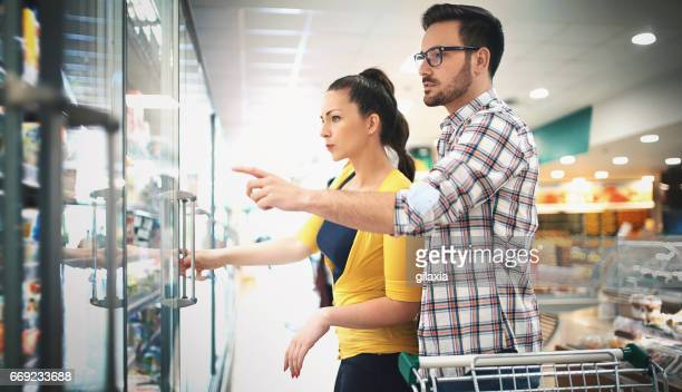buying food in supermarket - convenience store stock photos and pictures