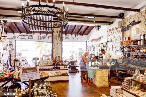buying souvenirs in greek gift shop on vacation - souvenir stock pictures, royalty-free photos & images