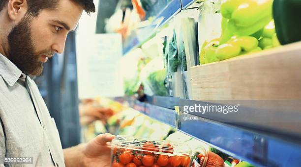 Buying vegetables in supermarket.