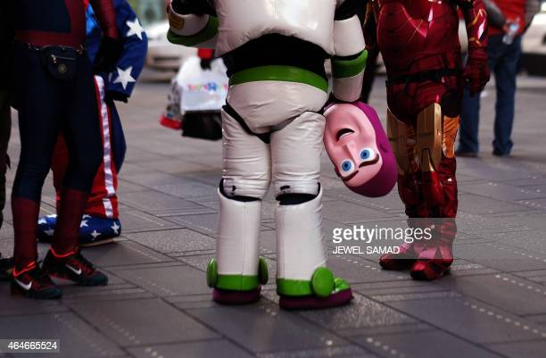 'Buzz Lightyear' holds his 'head' as he confers with other dressed up superheroes and cartoon characters at Times Square in New York on February 27...