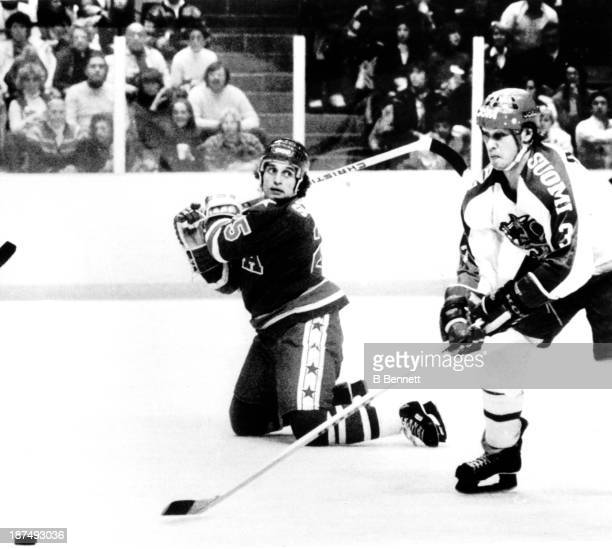 Buzz Schneider of the USA looks as though he is about to whack Seppo Suoraniemi # of Finland during the Gold Medal game in the 1980 Winter Olympics...